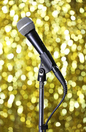 amplified: Microphone on stand on golden background