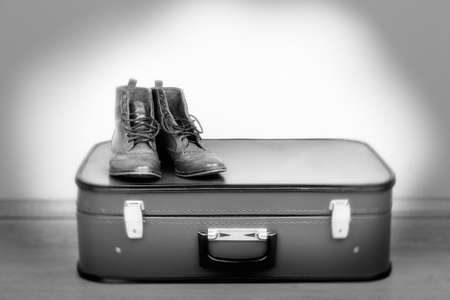 shades of grey: Vintage suitcase with male shoes on floor in shades of grey Stock Photo