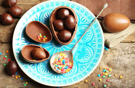 Chocolate Easter eggs on color plate, on wooden background photo