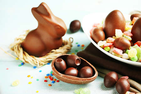 chocolate eggs: Chocolate Easter eggs and rabbit on plate, on color wooden background Stock Photo