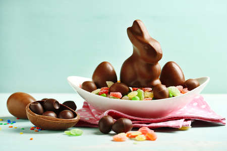 sweet: Chocolate Easter eggs and rabbit on plate, on color wooden background Stock Photo