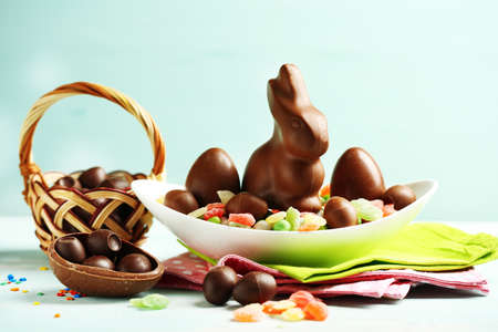 Chocolate Easter eggs and rabbit on plate, on color wooden background Stock Photo