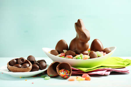 egg shape: Chocolate Easter eggs and rabbit on plate, on color wooden background Stock Photo
