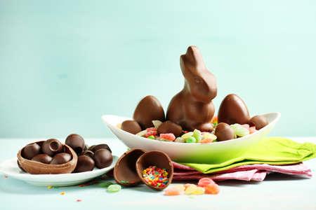 pascuas navide�as: Chocolate huevos de Pascua y conejos en la placa, en el color de fondo de madera Foto de archivo