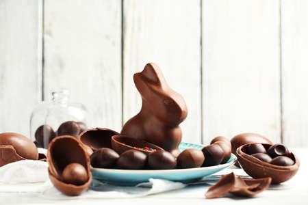 huevo: Chocolate huevos de Pascua y conejos en la placa, en el color de fondo de madera Foto de archivo