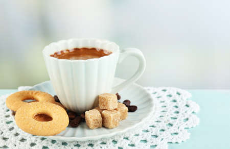 Cup of coffee and tasty cookies on color wooden table, on light background photo