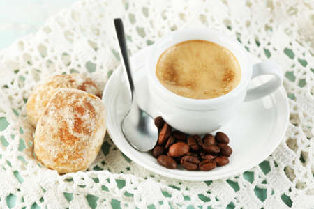 Cup of coffee and tasty cookie on color wooden background photo