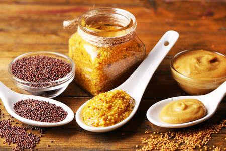 Semi di senape, polvere e salsa in cucchiai, ciotole e barattolo di vetro su fondo di legno Archivio Fotografico - 40648834