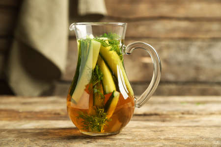 ewer: Glass ewer with fresh organic cucumber water on wooden table