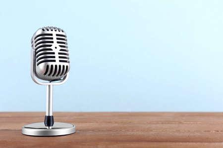 microfono antiguo: Micrófono retro en mesa de madera sobre fondo claro