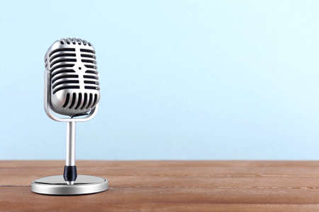 Retro microphone on wooden table on light background
