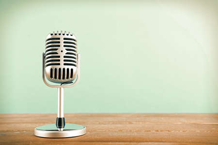Retro microphone on wooden table on blue background Foto de archivo