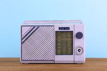 shortwave: Retro radio on wooden table on light colorful background