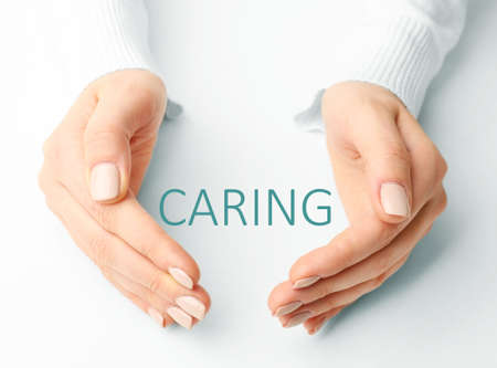 health care provider: Female hands with word caring on light background