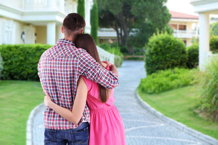 hand holding house: Loving couple looking at their dream house