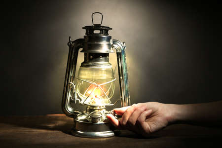 inflammable: Hand lights a kerosene lamp on dark grey background Stock Photo