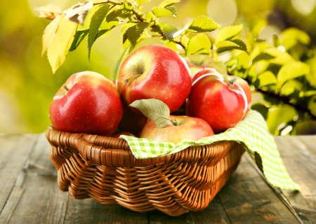 canasta de frutas: Cesta de mimbre de manzanas rojas con la servilleta sobre la naturaleza de fondo Foto de archivo