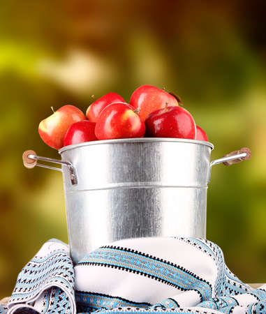 dishcloth: Pail filled with red apples and dishcloth on bright background
