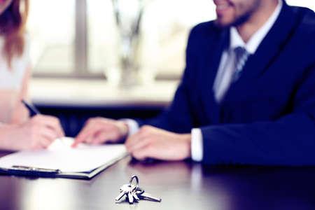 firmando: Firma del contrato y las llaves en la mesa, primer plano Foto de archivo