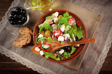 food dish: Bowl of Greek salad served on napkin on wooden background closeup