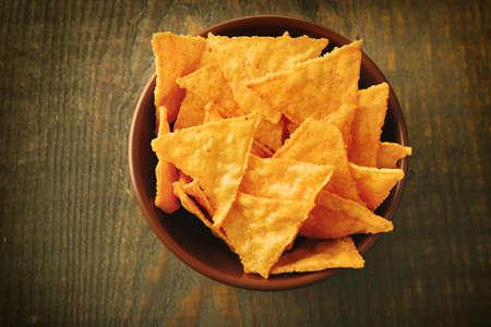 nacho chip: Tasty nachos in color bowl, on wooden background