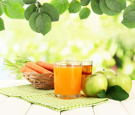 carrot: Glasses of juice, apples and carrots on table on natural background Stock Photo