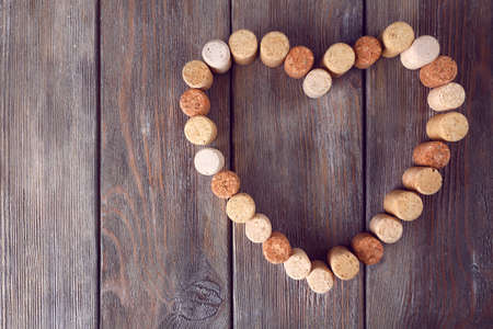 Heart shape of wine corks on rustic wooden planks background