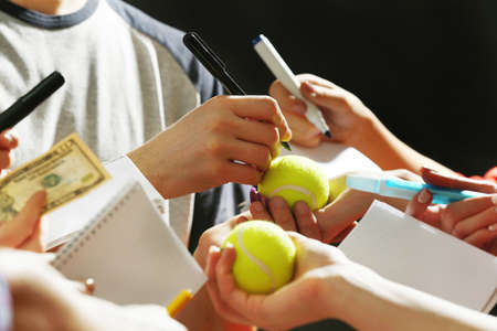 popularity: Sportsman signing autograph on tennis ball on dark background
