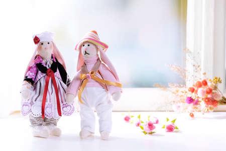 Handmade dolls near window close-up photo