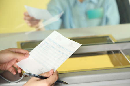 Teller window with working cashier and female hands with claim check. Concept of payment of utilities Stock Photo