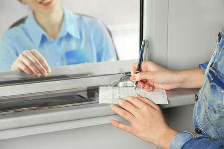 Teller window with working cashier and female hands with claim check. Concept of payment of utilities Фото со стока