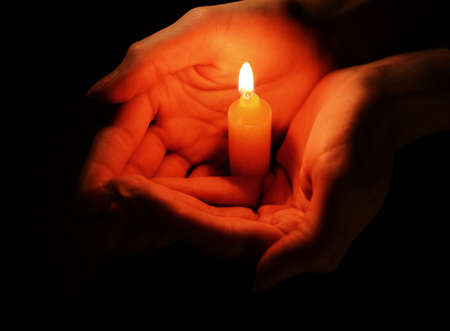 hands fire passion: Candle in female hands on black background