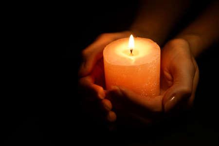 kerze: Kerze in weiblichen Händen auf schwarzem Hintergrund