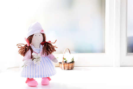 Handmade doll near window close-up photo