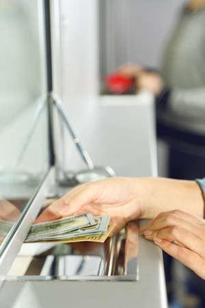empleados trabajando: Mano femenina con el dinero en la ventana del departamento de caja. Concepto de intercambio de moneda