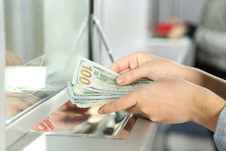 cash on hand: Female hand with money in cash department window. Currency exchange concept