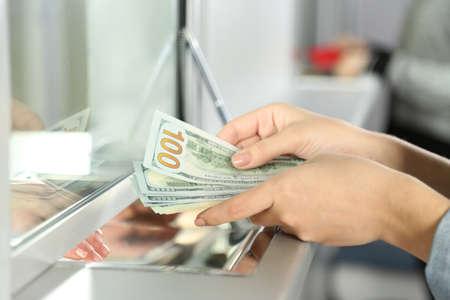 mostradores: Mano femenina con el dinero en la ventana del departamento de caja. Concepto de intercambio de moneda