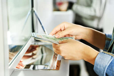 gain money: Main Femme avec de l'argent dans la fenêtre du département de trésorerie. Devise notion de change