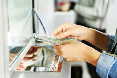 dinero: Mano femenina con el dinero en la ventana del departamento de caja. Concepto de intercambio de moneda