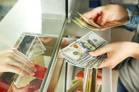 Vrouwelijke hand met geld in contanten afdeling venster. Valuta exchange concept Stockfoto