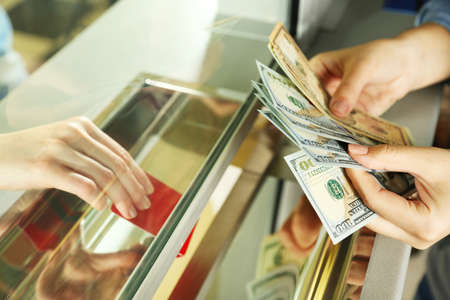 currency: Female hand with money in cash department window. Currency exchange concept