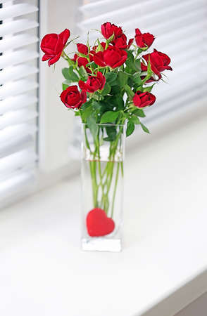 Bouquet of red roses in glass vase with heart on windowsill background photo