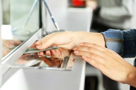 pieniądze: Kobieta strony z pieniędzmi w oknie działu pieniężnych. Waluta wymiany koncepcji