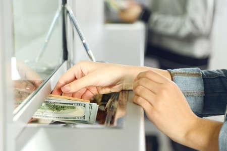 pracoviště: Ženská ruka s penězi v hotovosti oknem oddělení. Výměna koncepce měny Reklamní fotografie