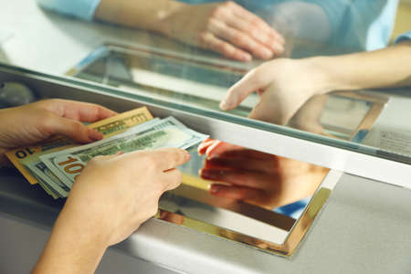 departments: Female hand with money in cash department window. Currency exchange concept