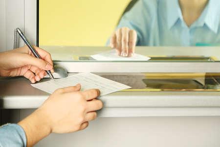 cuenta: Ventanilla con cajero y manos femeninas trabajando con cheque reclamación. Concepto de pago de los servicios públicos Foto de archivo