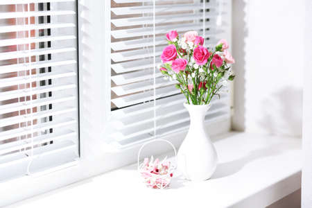 Bouquet of pink roses in white vase on windowsill background