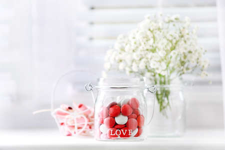 Sweet candies in jar with flowers on windowsill background photo