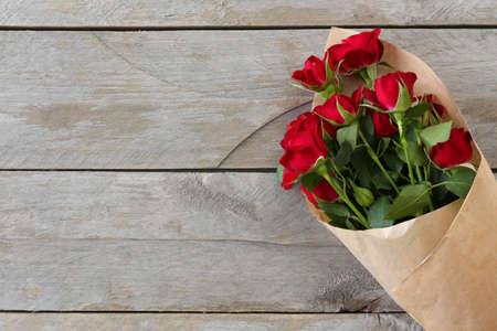 Red roses wrapped in paper on wooden table background Stockfoto