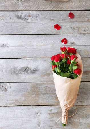 Red roses wrapped in paper on wooden table background Stock Photo